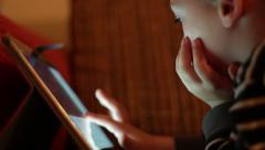 Kid chooses cartoons on YouTube by sliding his finger on the touch screen Stock Footage