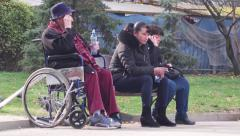 Stock Video Footage of A disabled woman sitting in a wheelchair at the park, and next to it is smoke