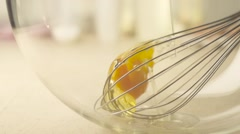 Egg yolks and whisk in a glass bowl - stock footage