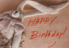 Felt doll on background with message Happy birthday - stock photo