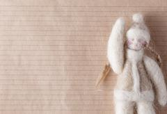 Felt doll on background with space for you message - stock photo