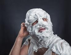 Crazy man with face completely in shaving foam Stock Photos