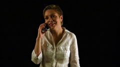 Short hair girl talking by mobile phone over black - stock footage
