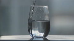Slow motion water being poured into glass cup. Stock Footage