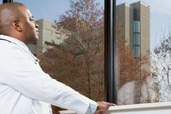 Doctor looking out of window Stock Photos