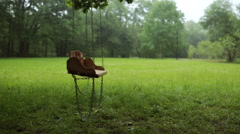 Empty wooden swing swaying slowly in the rain Stock Footage