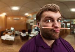 Strange man holds pencil with his nose and lips Stock Photos
