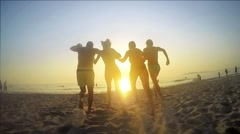 Young family running happily in water sunset and splashing ocean SLOW MOTION - stock footage
