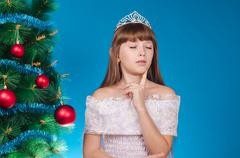 The girl with a diadem on the head costs near an elegant New Year tree and ma - stock photo