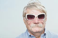 Senior man wearing a tiara and sunglasses - stock photo