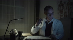 Stressed doctor working at his office desk - stock footage