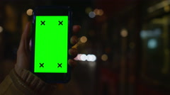 4K Close up of hand using a smartphone with green screen display outdoors Stock Footage