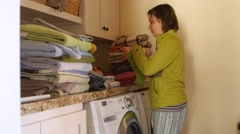 A tired mother folds piles of laundry in room Stock Footage