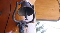 Hand rings a fun steer bell at the house Stock Footage