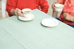 Two senior women drinking tea outdoors Stock Photos
