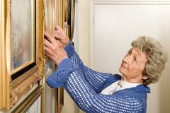 Woman adjusting picture frames Stock Photos