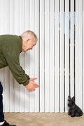 Elderly man beckoning dog ornament Stock Photos