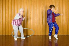 Two senior women exercising with hula hoops - stock photo