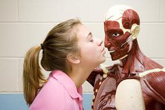 Female student kissing an anatomical model - stock photo