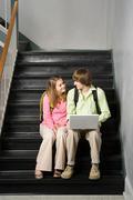 Teenage couple sat on school stairway Stock Photos