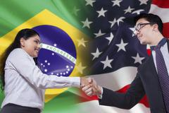 Brazilian woman shaking hands with American person - stock photo