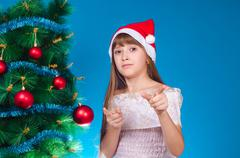 The girl with a red cap on the head costs near a beautiful New Year tree and  Stock Photos