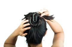 Rear view of brunette girl making hair bun - stock photo