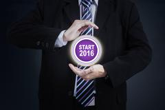 Hands protect start button with numbers 2016 Stock Photos