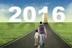 Little girl and dad walk toward number 2016 - stock photo