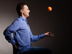 Diet and healthy nutrition. Man throwing orange Stock Photos