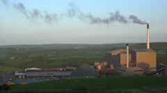 An industrial plant belching smoke in the green rolling hills of England, Stock Footage