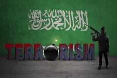 Rebel with flag of Saudi Arabia and weapon - stock photo