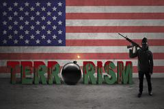 Terrorist holds rifle with American flag - stock photo