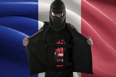 Terrorist with time bomb and flag of France Stock Photos