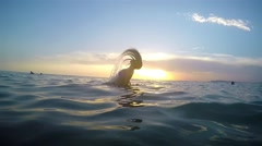 Woman makes spiral splashing water with her hair at sea sunset surface. SLOW Stock Footage