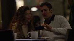 4K Happy attractive couple pose for a selfie at cafe table in the city at night Stock Footage