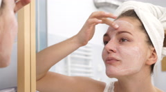 Woman applying mask cream on face in bathroom 4K Stock Footage