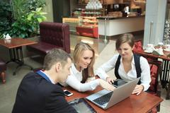 Businessmen sitting in cafe for a laptop, discussing plans. two girls and man - stock photo