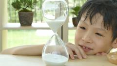 Boy looking at hourglass Stock Footage
