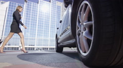 4K Beautiful businesswoman traveling - loading suitcase into car in car park Stock Footage