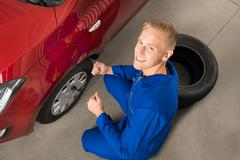 High Angle View Of Mechanic Changing Tire In Garage With Wrench Stock Photos