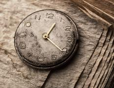 Old clock on a manuscript book - stock photo
