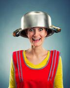 Happy housewife with sause pan on her head Stock Photos