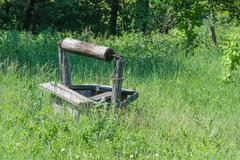 Abandoned wooden well - stock photo