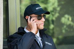 Portrait Of Young Security Guard Talking On Walkie-talkie Stock Photos