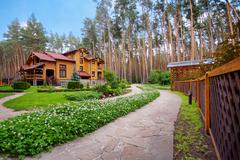 Big wooden mansion in pine forest Stock Photos