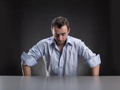 Suspicious man sits at table - stock photo