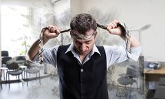 Agressive businessman with a tie on his head - stock photo