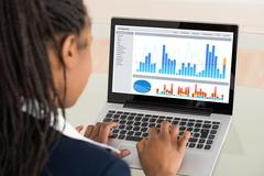 Close-up Of A Young Businesswoman Analyzing Graph On Laptop Stock Photos
