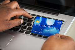 Close-up Of A Person's Hand Using Debit Card While Shopping Online On Laptop Stock Photos